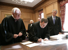 Chief Justice John Roberts signing document • Photo by Eric Draper • WikiCommons