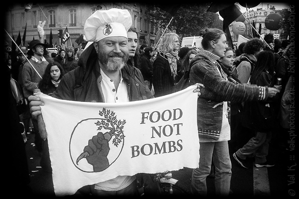 Black and white photo of man in chef hat and banner